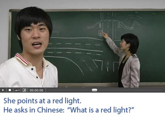 Screenshot of a video with professional Chinese actors on which one sees what he hears. She points at a red light. He asks: What is a red light?